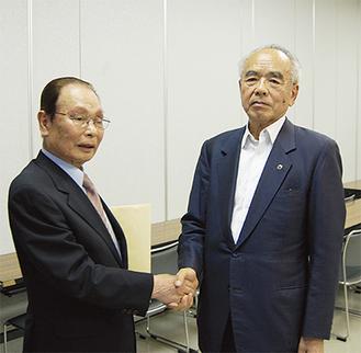 前会長・宮田良辰氏(左)からバトンを渡される吉崎隆男会長