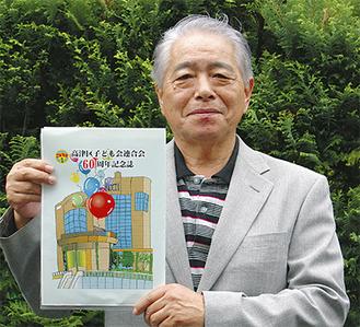 完成したばかりの記念誌を手にする新井さん