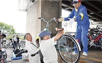 解体した自転車をトラックに乗せる市民