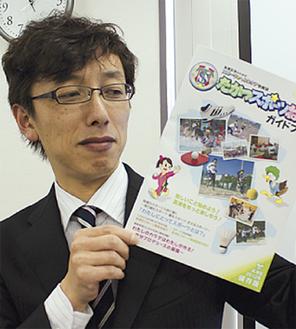 冊子を手にする同NPOの岩嵜司さん