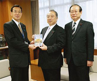 渡邊教育長にDVDを手渡す大島議長(中央)と岩崎副議長(右)