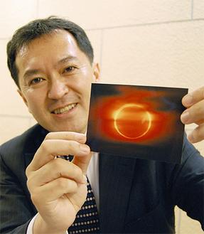 夕暮れ時の金環日食の写真を手にする高田さん(2010年、中国の青島で撮影)