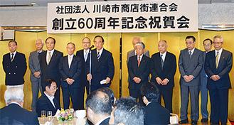 祝賀会で役員とともに挨拶にたつ尾澤会長