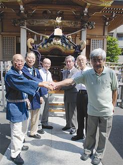 神輿の前で握手。(左から)戸張さん、吉田さん、長崎宮司、神山宮司、猪狩さん、熊谷さん