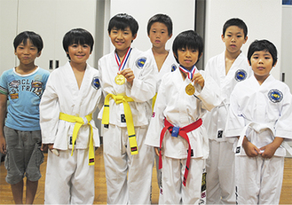 金メダルをかかげる阿部君(左)と山内君(右)を囲む同じ道場の選手