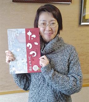 記念誌を手にする写真撮影担当の佐藤さん