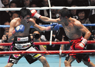 王者レベコ選手(右)の猛攻を受けながらも、下がらずにジャブを繰り出す黒田選手