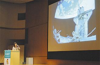 宇宙から見た地球をスクリーンに映し、講演する山崎さん