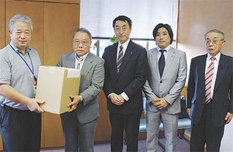 秋岡区長(左)に歯ブラシを手渡すクラブのメンバー