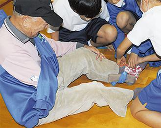 地域住民がけが人役となり、身近な道具で応急手当