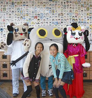 記念事業の一環として在校生一人ひとりの顔を描いて制作したタイルを背に松島さん(左)と山口さん、着ぐるみは100周年記念のキャラクター