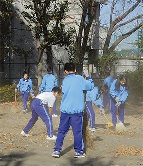 公園の落ち葉を拾う生徒たち