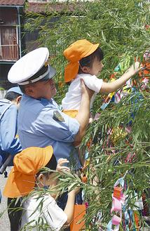 警察官に抱き上げられ、園児たちが短冊を結んだ