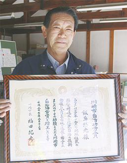 表彰状を手にする飯島会長