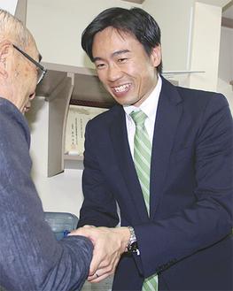 支援者と握手する3期連続トップ当選の青木氏