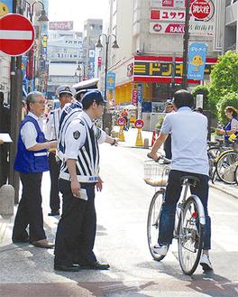 一方通行の逆走を注意する署員と区民会議のメンバー
