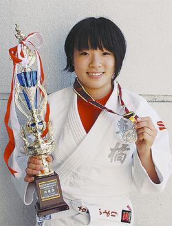 メダルとトロフィーを手にする古賀さん