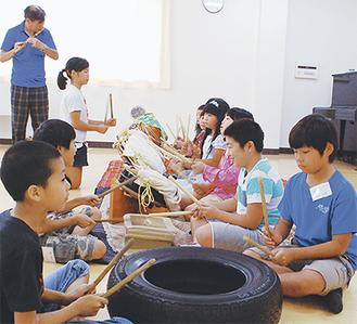 笛を吹きながら指導する石田さんと児童たち