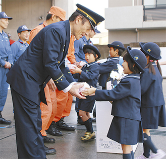 高津消防署の森下泰弘署長(左)に感謝のプレゼントを手渡す園児