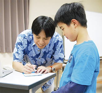 講演後に参加者と触れ合う藤原さん(左)