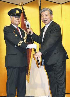 河原前団長(右)から団旗を受け取る森新団長