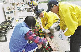 一緒に花植えを楽しむ生徒と会員ら