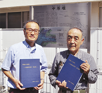 記念碑の前で冊子を手にする井上さん(右)と朝山さん