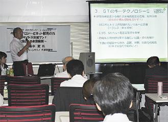 講演する田中社長(写真左)