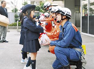 消防署員にリンゴを渡す園児たち