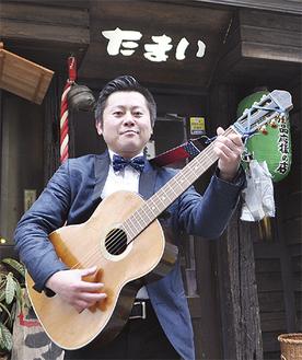 たまい本店前でギターを構える渡辺さん