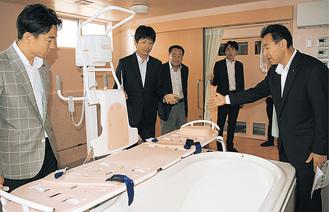 浴室設備の説明を受ける山際議員(右)