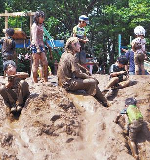 土山で遊びたわむれる子どもたち