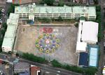 創立50周年記念の航空写真。デザインの元になった校章は初代校長、伊従寅雄氏の図案によるもの。梅の花の中に川崎市のマークを入れ、中央に「坂戸」を配す。梅の花の花弁に描かれた点々は児童を表している。写真提供:(株)フォトスタッフ