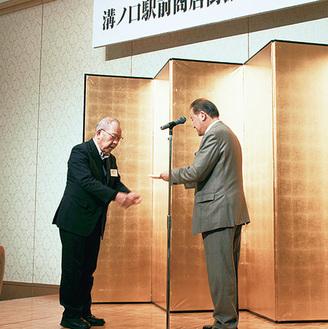 持田理事長から記念品を受け取る五味前専務理事(写真左)