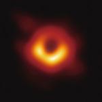 撮影に成功した写真。オレンジ色に光っているのは今まさに吸い込まれる星の残骸(チリ)で、本体は黒円の中心なのだとか=提供写真=