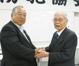 新会長の大島氏(左)と握手を交わす宮田氏