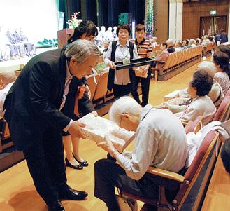 冨田会長から祝い品を受け取る参加者