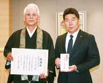 川崎市長に寄付した眞宗寺の小原住職(左)