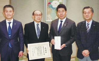 クラブメンバーと市役所を訪れ義援金を手渡した坂本会長(左から2番目)