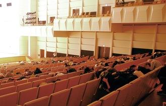 座席で屈み、頭を守る参加者たち