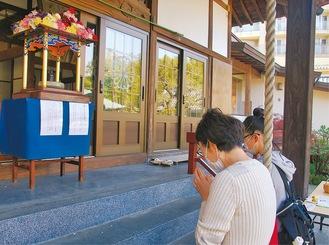 甘茶がけなしとなった花御堂の釈迦像に手を合わせる参拝者