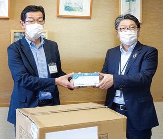 富士通ゼネラル社の担当者からマスクを受け取る鈴木哲朗区長(写真左・5月のセレモニーの様子)