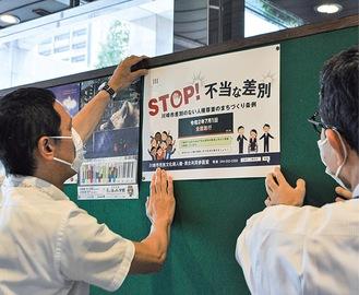 ポスターを掲示する市職員