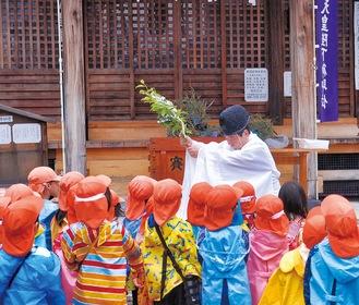 園児に向かって祈祷する金子宮司