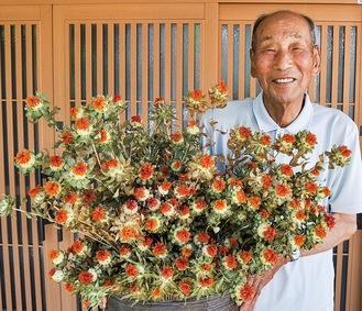 栽培した紅花を手にする高橋さん