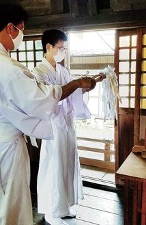 先輩の神職から手ほどきを受ける尹さん(写真右)