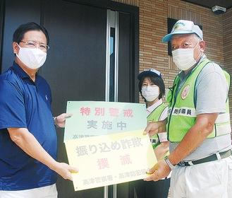 防犯指導員から看板を受け取る内田会長(左)