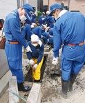 台風通過後、側溝の汚泥除去を行う消防団員