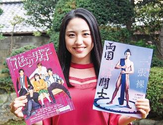 過去出演作品と次回作のポスターを手に笑顔の加藤さん