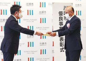 市長から表彰状を手渡される受賞者(右)